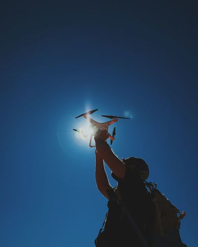 Low angle view of man holding quadcopter against clear blue sky