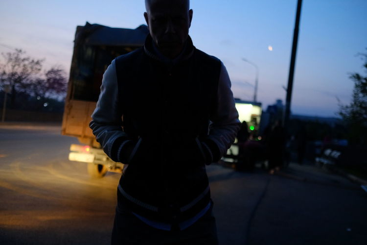 Rear view of man standing on road at sunset