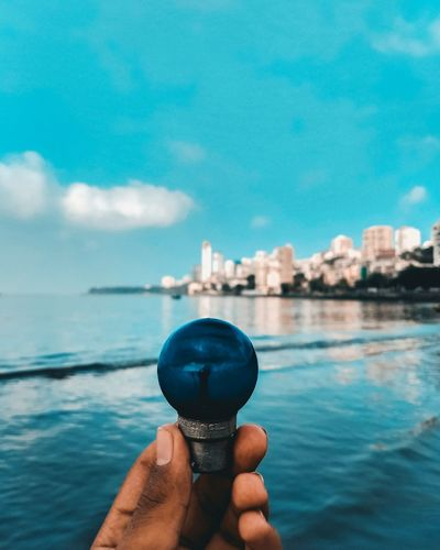 Bulb 💡 Bulb Blue Teal Blue Sky EyeEm Selects Human Hand City Water Cityscape Sea Urban Skyline Women Skyscraper Holding Personal Perspective Horizon Over Water Illusion Wave Beach Sandy Beach Seascape Ocean Calm