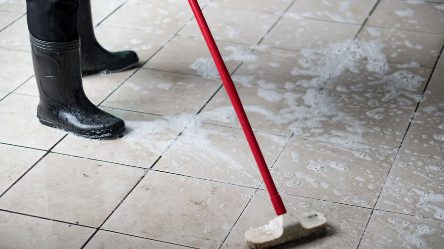 Low section of person wearing rubber boots while washing tiled floor