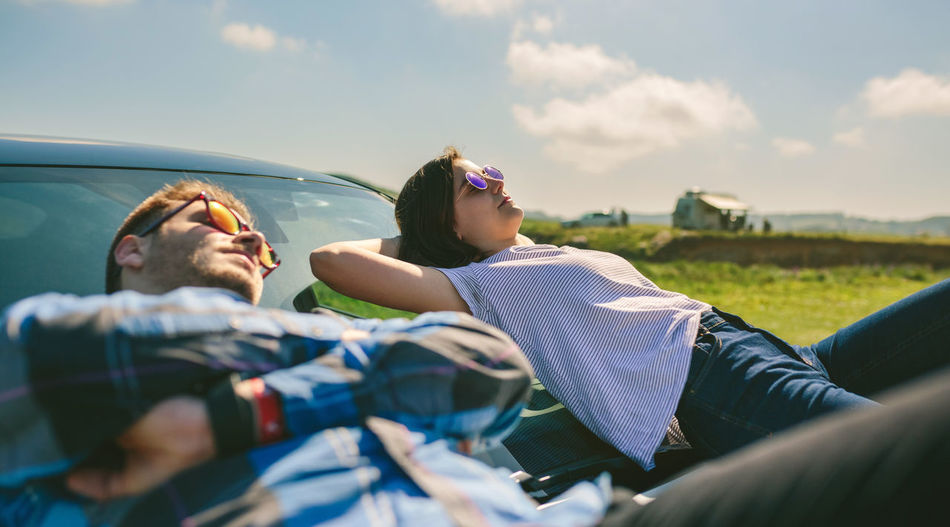 Man and woman relaxing on car against sky