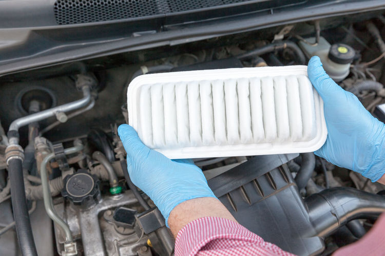 Holding new car engine air filter Human Hand Holding Protective Glove Working Repairing Service Equipment Mechanic Car Mechanic Replace Replacement Car Service Auto Mechanic Automobile Air Filter Filter Engine Vehicle Maintain Maintainance Airflow Combustion