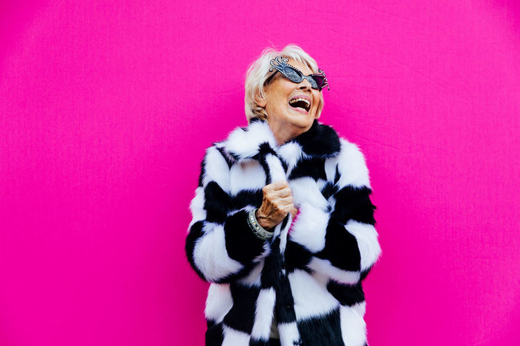 Senior woman laughing while standing against pink background