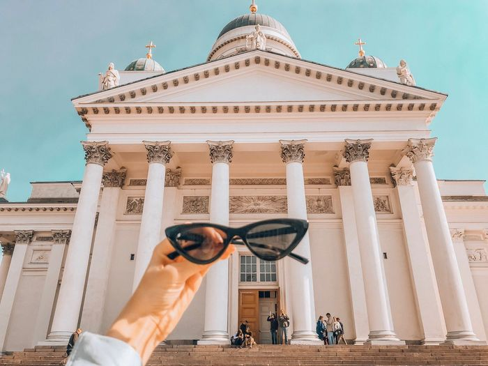 Cropped hand of woman holding sunglasses against cathedral