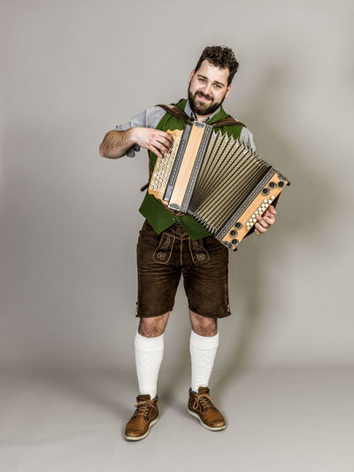 Musician Costume Leather Trousers Tradition Traditional Austria Green Pose Accordion Man Young Shorts Friendly Proud Happy Play Music Fun Joy Single One Background Copy Space Studio Entertainment Mountains Shirt STAND Hobby Leisure Cool Studio Shot Front View Indoors  Full Length One Person White Background Portrait Looking At Camera Casual Clothing Beard Facial Hair Mid Adult Men Holding Young Adult Standing Young Men Mid Adult Gray Background