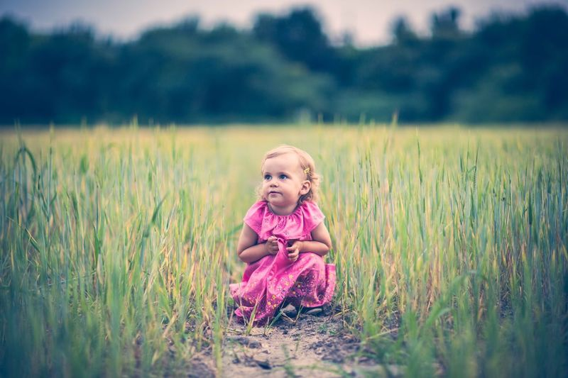 Portrait of young girl sitting on grassy field