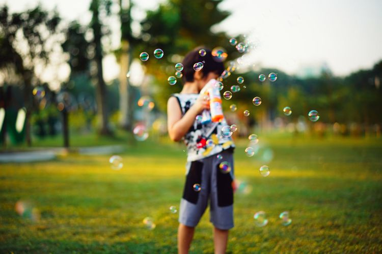 Boy Standing With Bubbles In Mid-Air At Park