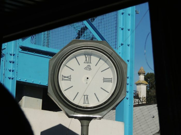 Close-up of clock by building seen through broken glass