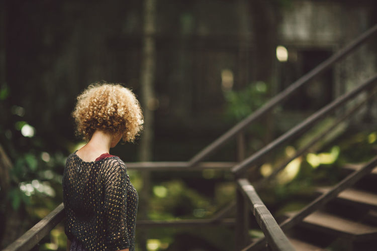 Side View Of Mid Adult Woman With Curly Hair Standing By Railing