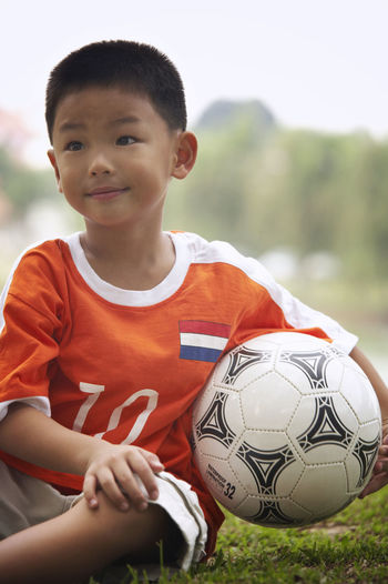 Smiling Of Boy With Soccer Ball Sitting On Field At Park