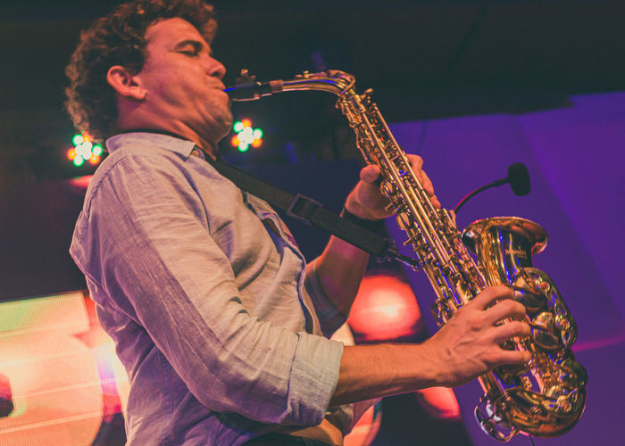 Low angle view of man playing saxophone at music concert