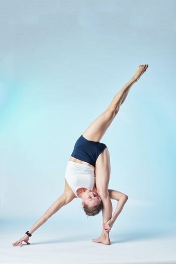 Full length of woman exercising against colored background