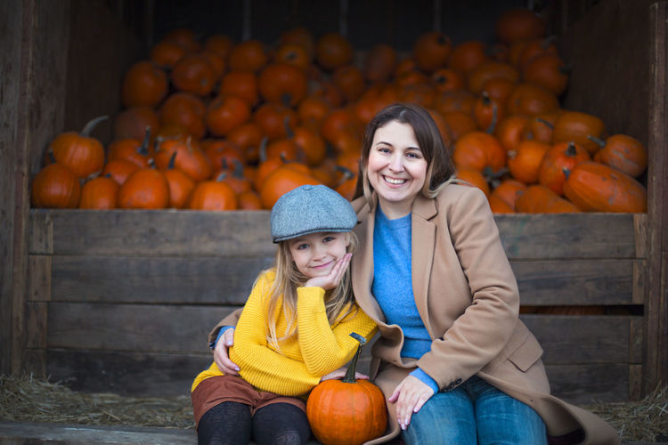 Portrait of smiling woman and daughter sitting against pumpkins