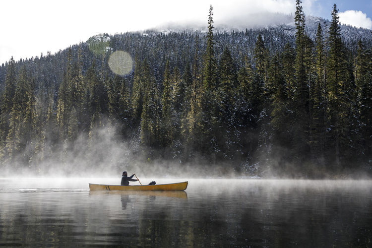 Man on boat in lake against mountain