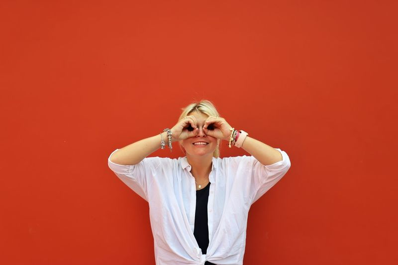 Portrait of smiling woman looking through hand masks against red background