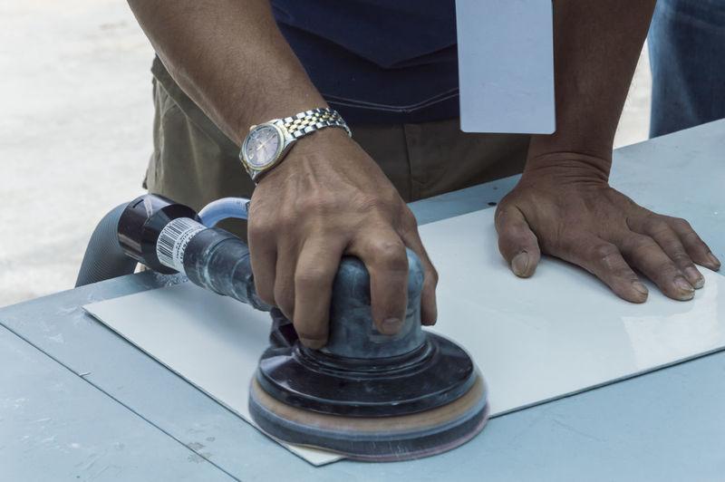 Midsection of man moving sander on tile