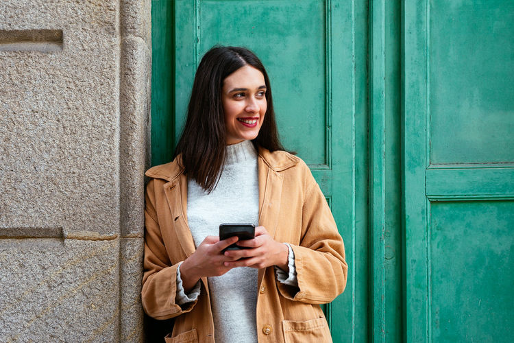 Young woman using mobile phone while standing against door