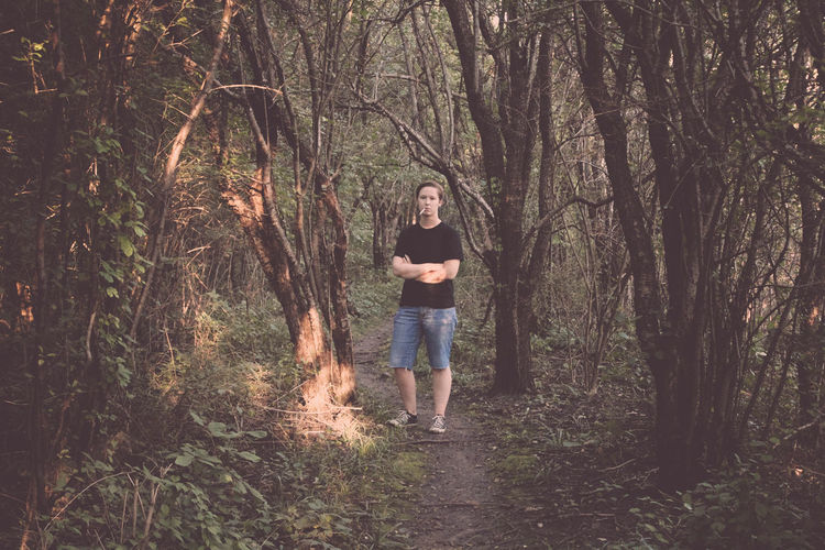 Full length portrait of young man standing with arms crossed in forest