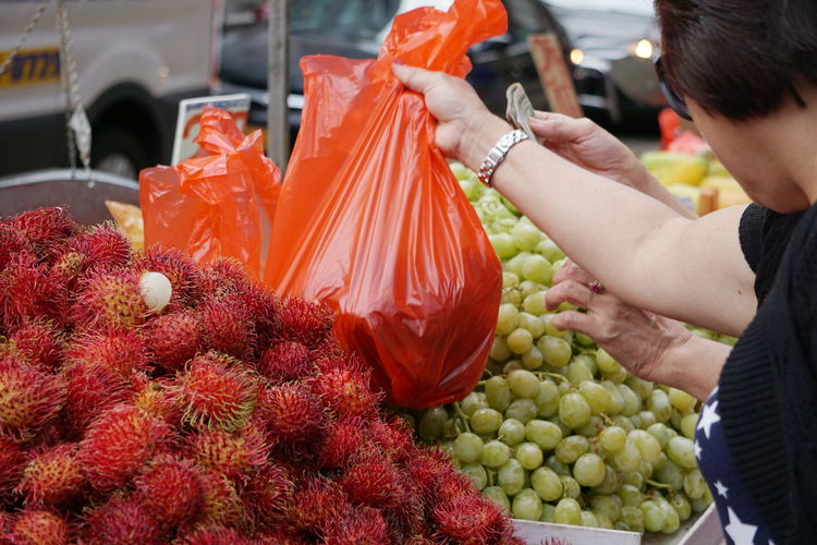 Women Buying Fruits From Market Stall