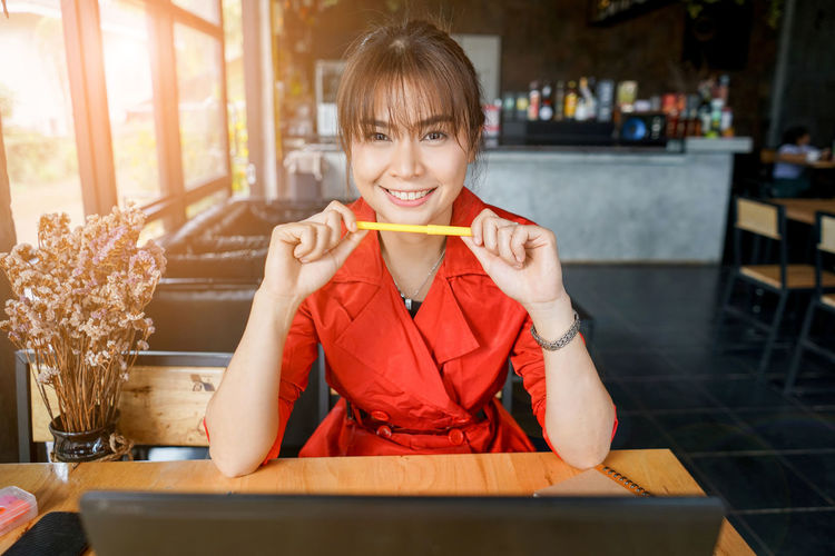 Portrait Of Smiling Woman Sitting At Table