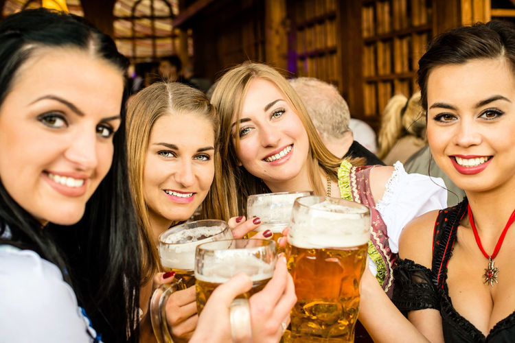 Portrait Of Happy Women Enjoying Beer At Oktoberfest