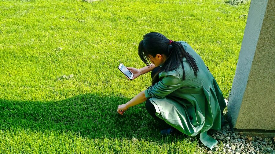 Woman using mobile phone on field