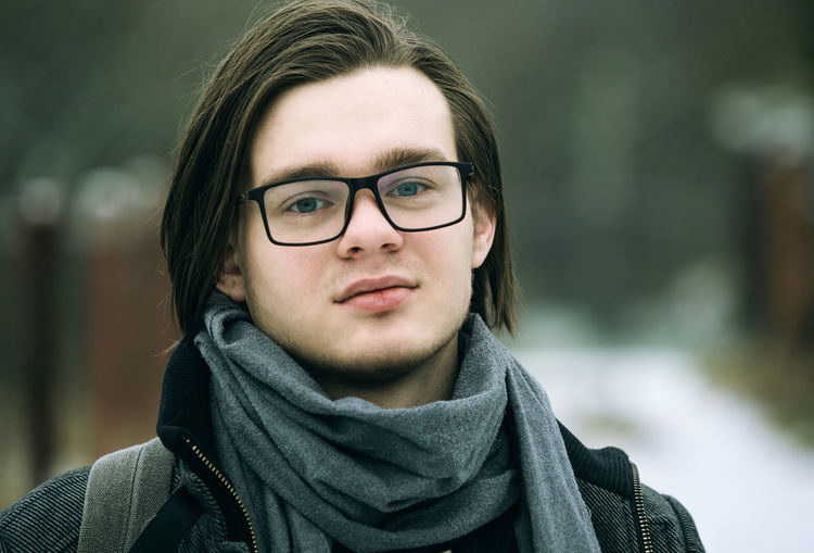 Young guy with glasses close-up face outdoors winter portrait