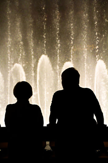 Rear view of silhouette man and woman standing against sky at night