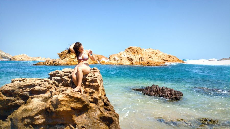 Full length of woman sitting on rock at beach against clear blue sky