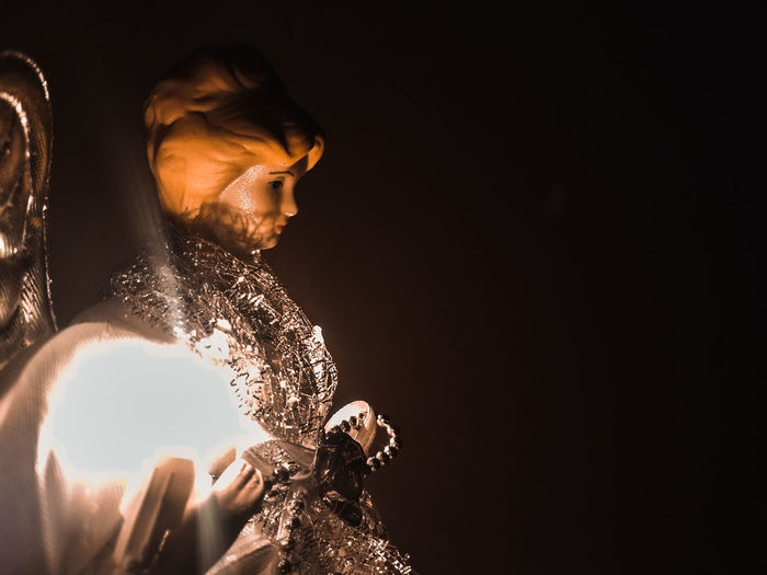 Sunlight falling on angel in darkroom