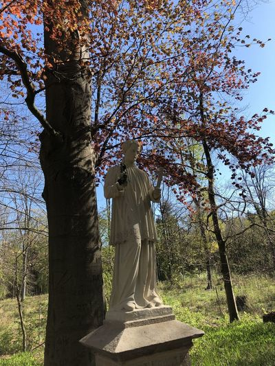 Statue amidst trees against sky