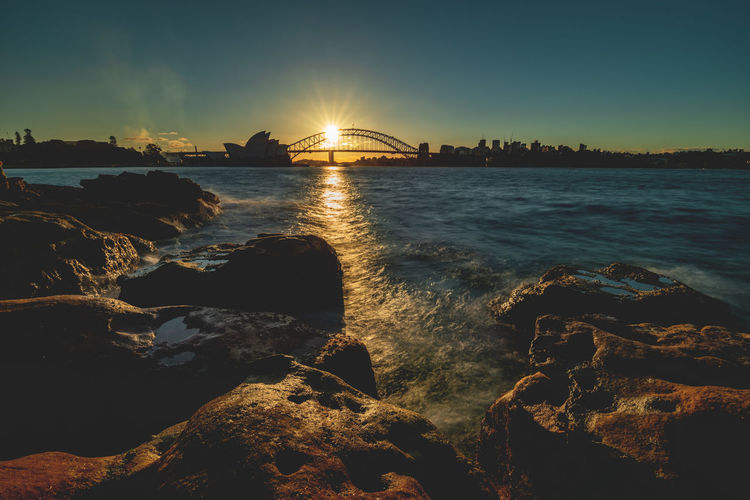 Sydney Harbour sunset overlooking the Opera House and Harbour Bridge. ❤️ Cityscape Discover Places Harbour Longtime Exposure Nikon D800E Silhouette Sydney Harbour Bridge Sydney Opera House Adventure Bridge Idyllic Motion Outdoors Reflections In The Water Rock Scenics - Nature Sky Sun Beams Sun Flare Sunlight Sunset Travel Destination Travel Destinations Water Waterfront