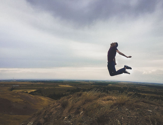 Man jumping on land against sky