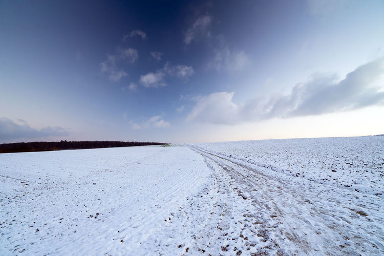 Scenic view of road against sky during winter