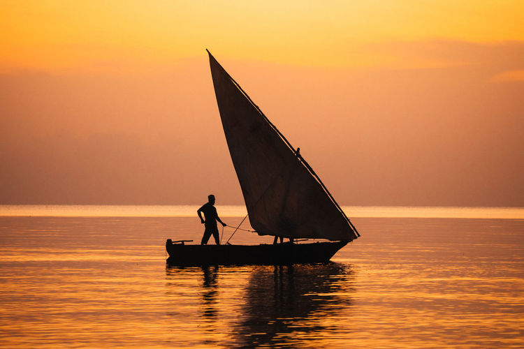 Silhouette man on sailboat in sea against sky during sunset