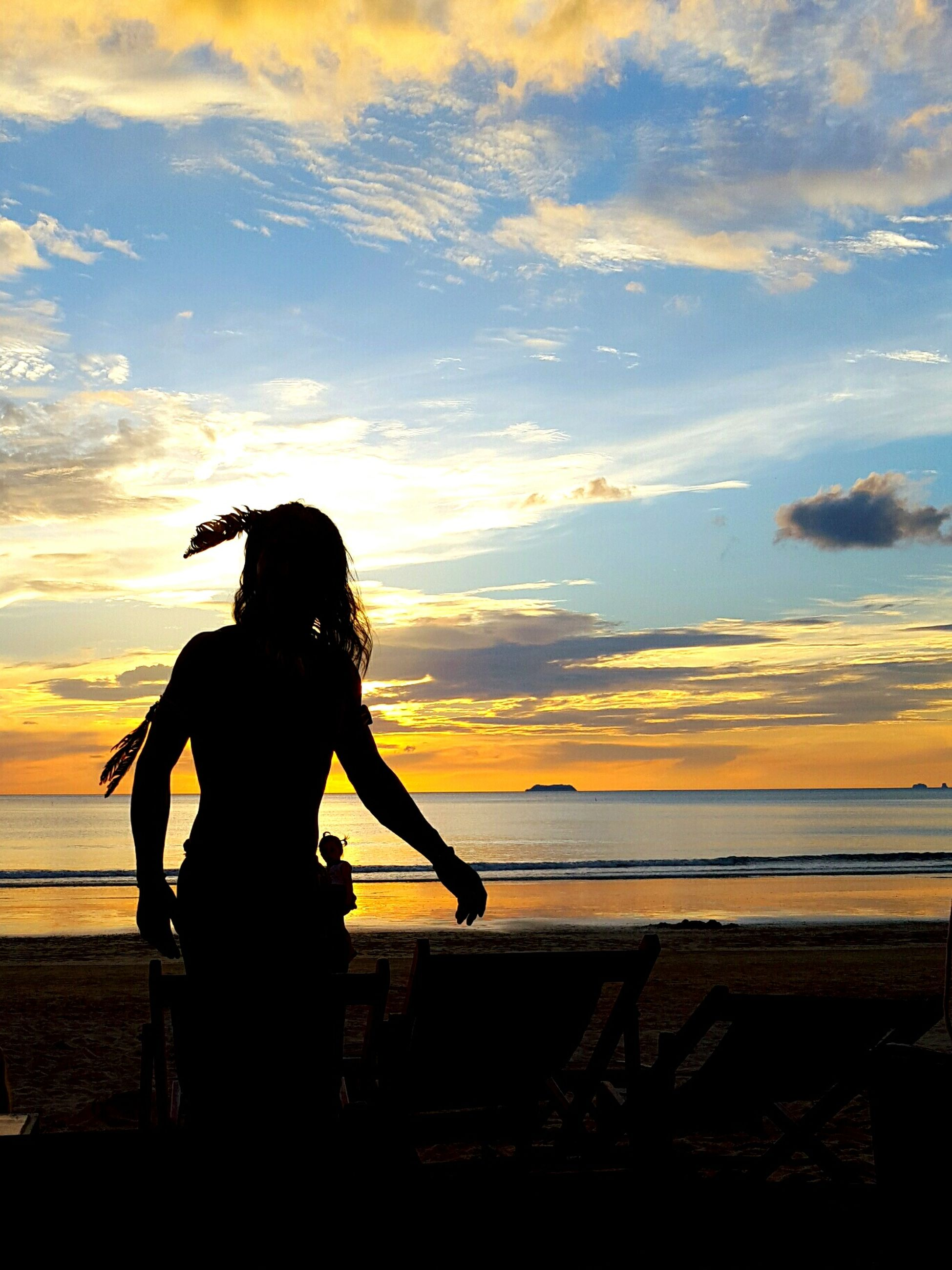 sunset, sea, horizon over water, lifestyles, sky, beach, silhouette, water, leisure activity, shore, orange color, person, beauty in nature, scenics, full length, standing, tranquility, tranquil scene