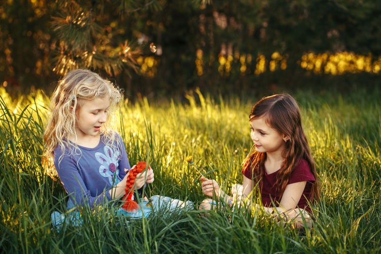 Friends playing with dolls on field
