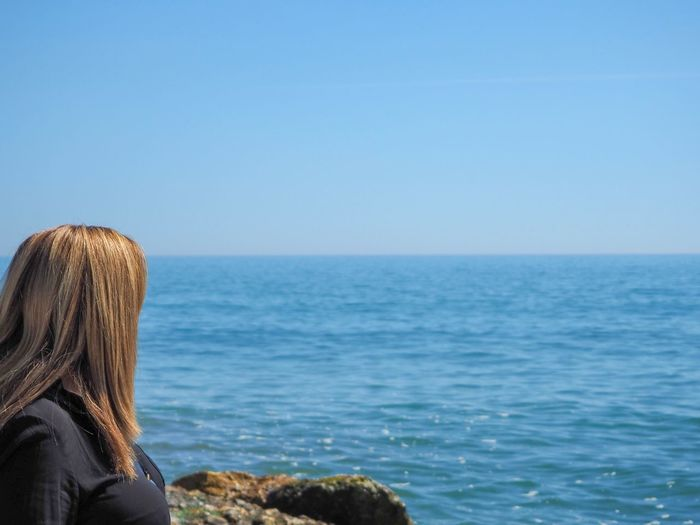 Side view of woman looking at sea against sky