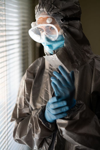 Woman wearing surgical mask and protective suit standing by window