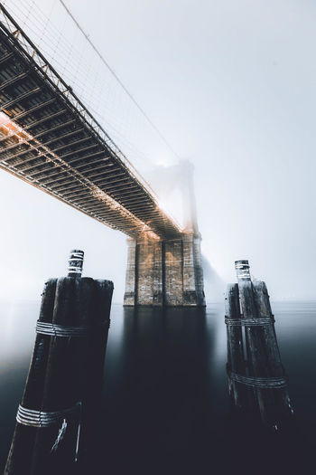 Low angle view of wooden posts against brooklyn bridge over east river