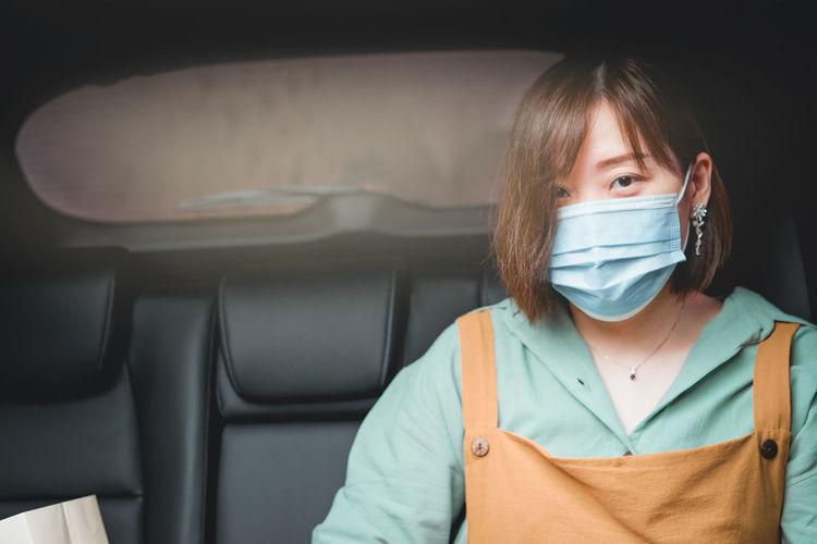 Portrait of woman wearing mask sitting in car