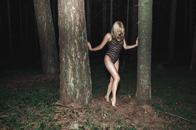 Sensuous woman wearing bodysuit while walking amidst trees at forest