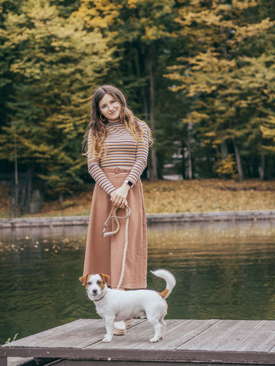 Portrait of young woman with dog in lake