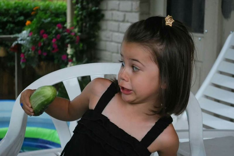 Girl with cucumber making a face