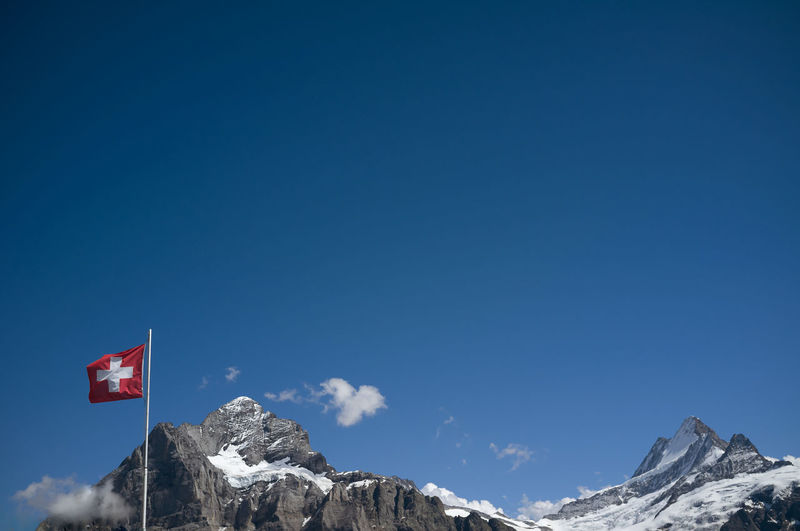 Low angle view of swiss flag against mountain and blue sky