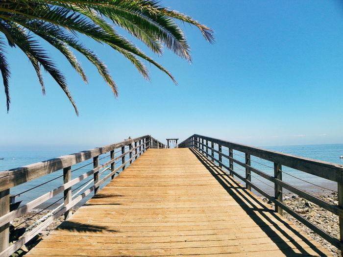 Beauty In Nature Blue Boardwalk Calm Day Diminishing Perspective Horizon Over Water Idyllic Jetty Long Narrow Nature No People Ocean Outdoors Pier Scenics Sea Sky The Way Forward Tranquil Scene Tranquility Vanishing Point Walkway Water