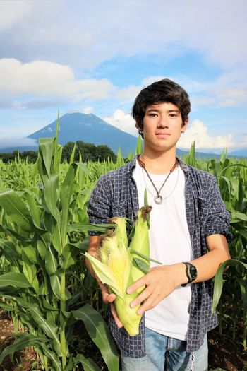 Freshly Picked Sweetcorn Farm Hokkaido Looking At Camera Mountain View Niseko Agriculture Casual Clothing Cloud - Sky Corn Farming Field Green Color Growth Holding Mountain Nature One Person Pick Your Own Plant Standing Sweetcorn Three Quarter Length Waist Up Young Adult Young Men This Is Strength 50 Ways Of Seeing: Gratitude This Is Natural Beauty The Modern Professional Human Connection Moments Of Happiness 2018 In One Photograph Redefining Menswear