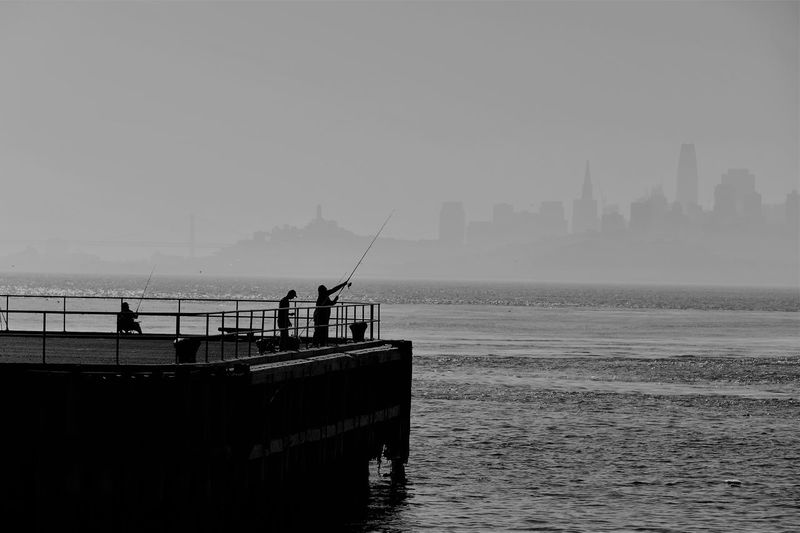 Silhouette people fishing on pier at sea against sky in city