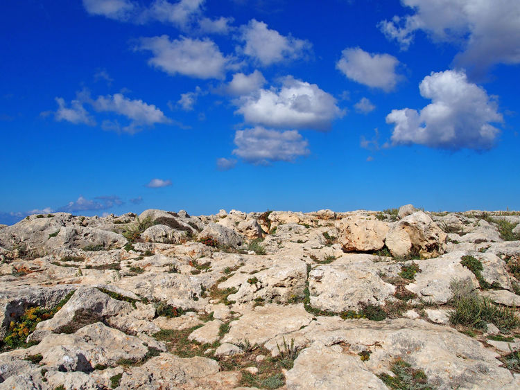 rugged rocky arid limestone pavement landscape with vegetation in the cracks and blue sunlit sky with white clouds Minorca Desert Limestone Sky Cloud - Sky Rock Scenics - Nature Beauty In Nature Solid Rock - Object Environment Tranquil Scene Tranquility Landscape Nature Blue Day No People Non-urban Scene Rock Formation Outdoors Remote Travel Climate Arid Climate