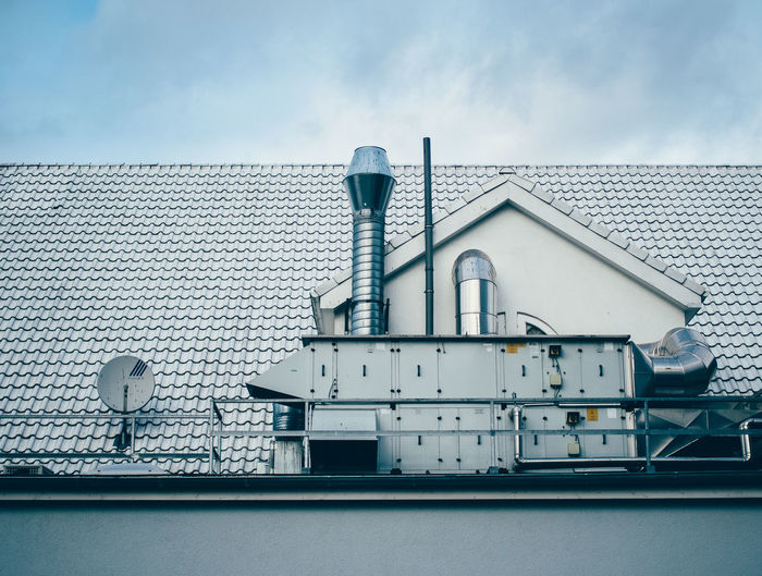 Low Angel View Of Machinery On House Rooftop Against Sky